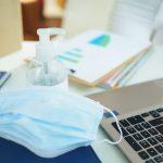 Masque chirurgical et gel hydroalcoolique sur un bureau